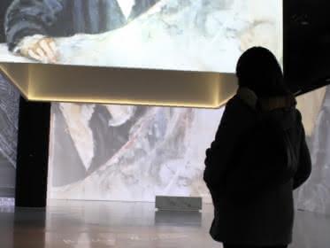 Photo d'une femme regardant une oeuvre sur un écran géant dans la première salle de visite Vision Impressionniste au château d'Auvers sur Oise