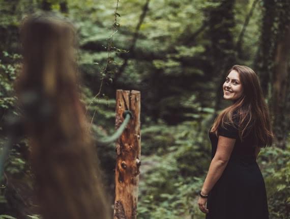 Photo d'une femme en robe noire se baladant en forêt