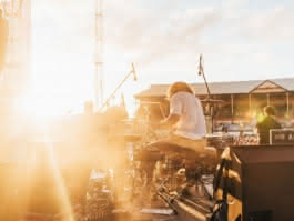 Photo d'un groupe de musique jouant devant un stade bondé sous un ciel bleu
