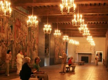 Photo de la galerie Psyché du château d'Ecouen appelé aussi musée national de la Renaissance dans le Val d'Oise, avec des visiteurs admirant les tapisseries aux murs