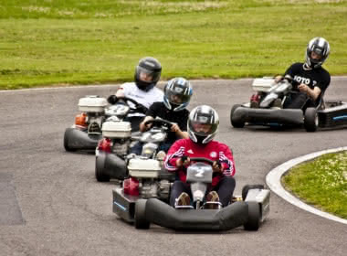 Photo de quatre hommes en train de conduire des kartings sur un circuit