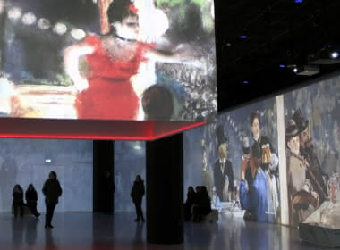 Photo de la première salle de visite de la vision impressionniste au château d'Auvers sur Oise, présentant sur des écrans plusieurs tableaux dont un avec une femme à robe rouge, du public regarde les tableaux
