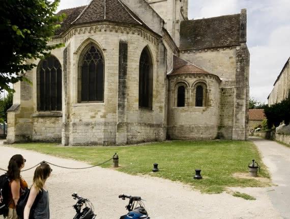 Photo de deux femmes à côté de leurs vélos regardent l'Eglise d'Auvers sur Oise peinte par Vincent Van Gogh