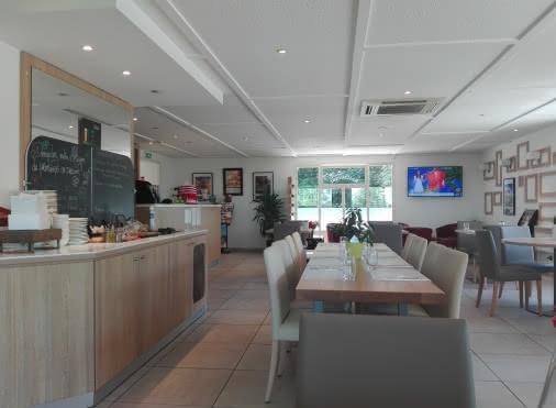 intérieur du restaurant avec les tables et au fond à gauche la documentation touristique