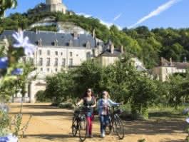Photo de deux cyclistes se baladant dans les jardin du château de la Roche Guyon. Le donjon surplombe les jardins en fleurs.
