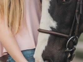 Photo d'une jeune fille blonde debout caressant le museau d'un cheval brun et blanc