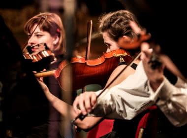 Photo de femmes jouant du violon sous une lumière tamisée