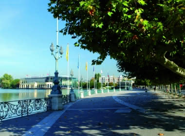 Photo de la promenade autour du lac d'Enghien-les-Bains avec vue sur le casino Lucien Barrière sous un ciel bleu