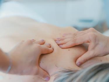 Photo de mains en train de masser le dos d'une femme au niveau des omoplates visiblement dans un centre de soin ou un spa
